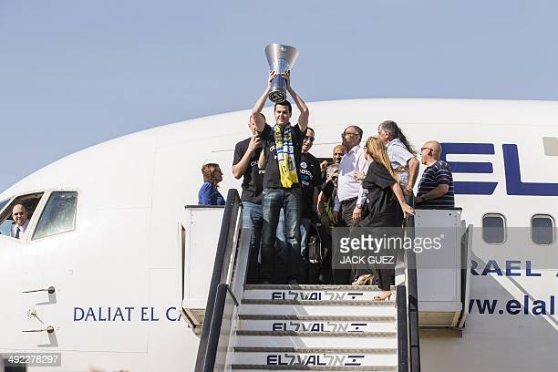Maccabi Tel Aviv forward Guy Pnini holds the trophy as the Israeli basketball team arrives at Ben Gurion airport on May 19 2014 after winning the...