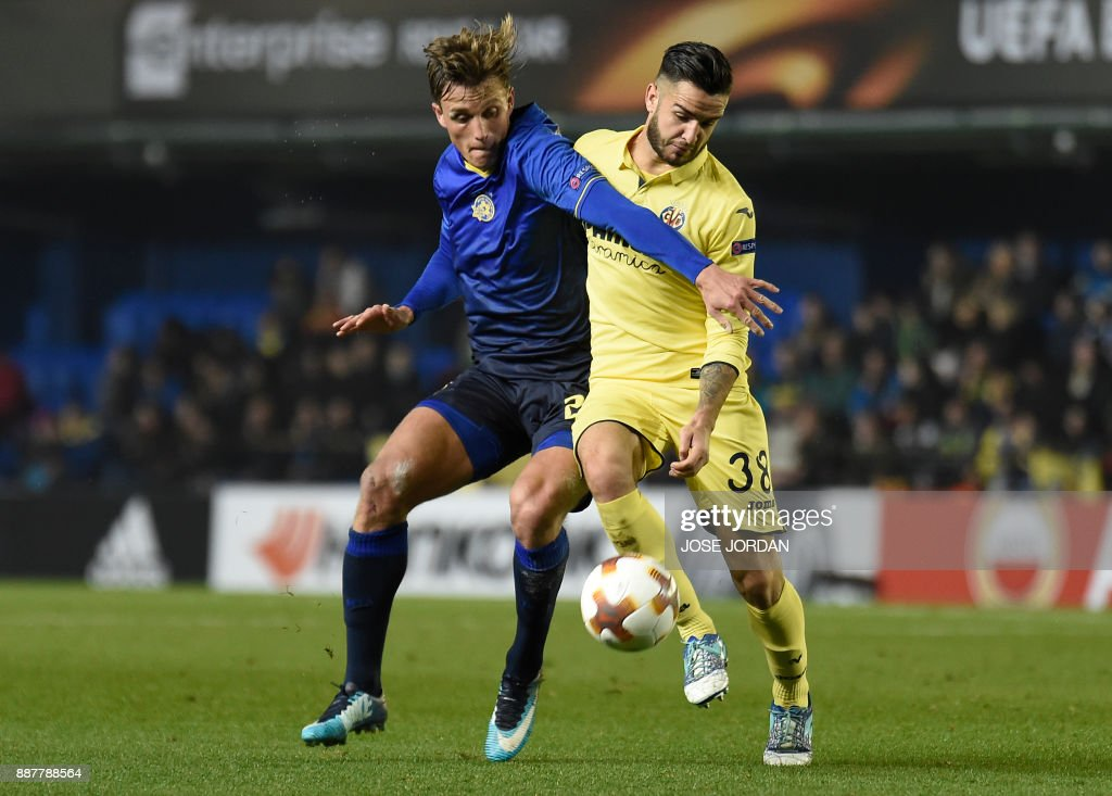 Maccabi Tel Aviv's forward Aaron Schoenfeld (L) challenges Villarreal's midfielder Genis Montolio during the UEFA Europa League group A football match between Villarreal and Maccabi Tel Aviv in Villarreal on December 7, 2017. /