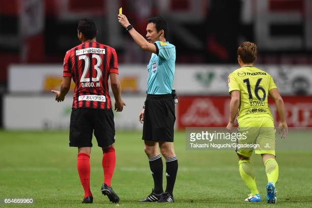 Macedo of Consadole Sapporo is shown a yellow card by referee Hiroyuki Kimura during the JLeague J1 match between Consadole Sapporo and Sanfrecce...