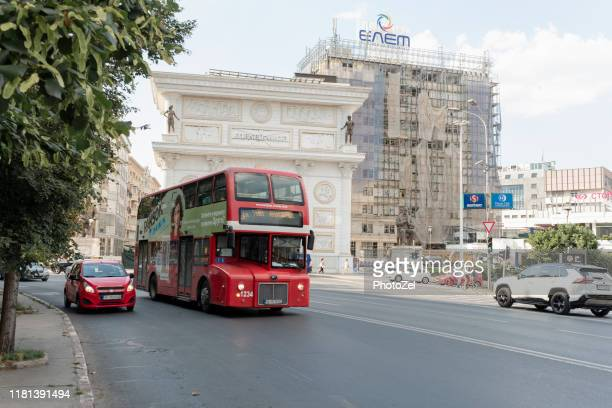 macedonia gate and double decker red bus - skopje stock pictures, royalty-free photos & images