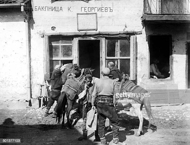men with their horses in front of a shop in Skopje April 1916