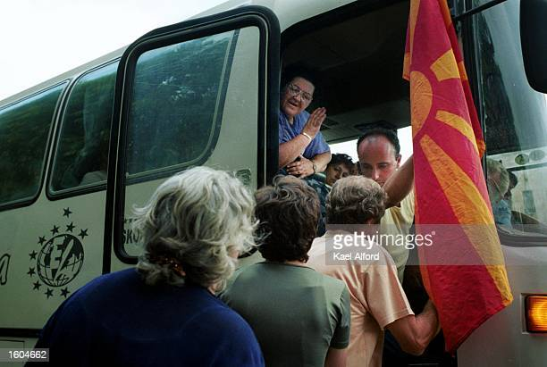 Macedonian civilians who had fled fighting between government troops and Albanian rebels board a bus to return to their home villages July 26 2001 in...