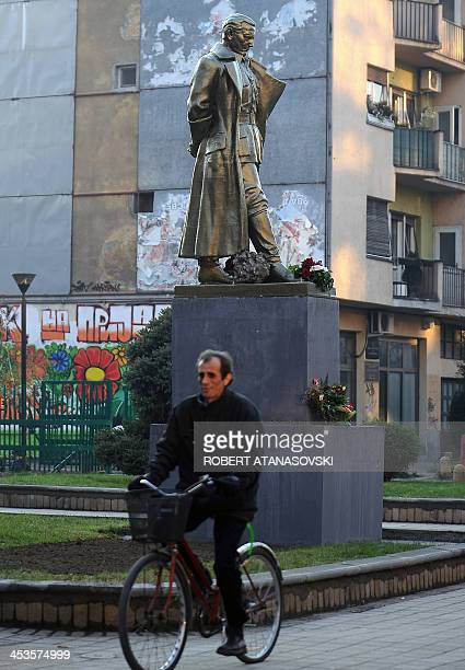 A Macedonian man rides his bicycle past a new statue of former Yugoslav leader Josip Broz Tito outside a high school bearing his name in Skopje on...