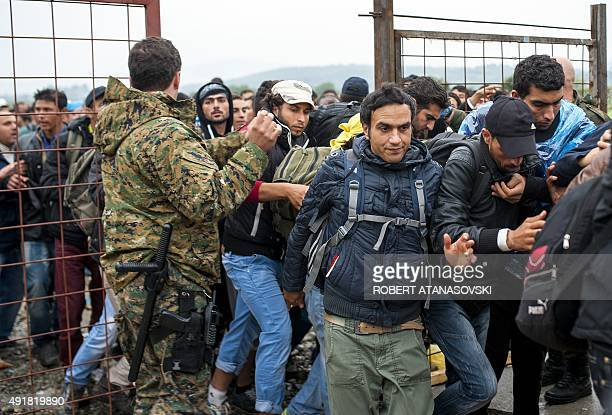Macedonian police officers control a crowd of migrants and refugees as they prepare to enter a camp after crossing the Greek border into Macedonia...