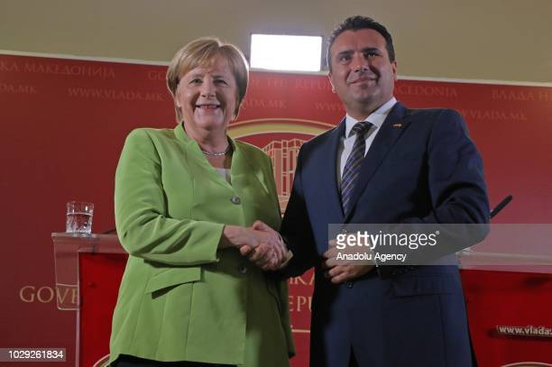 Macedonian Prime Minister Zoran Zaev and German Chancellor Angela Merkel shake hands as they pose for a photo after a joint press conference in...