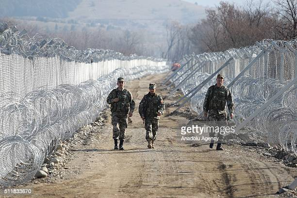 Macedonian soldiers walk on a path between the barbed wires in Gevgelija Macedonia after 80 Afghan and Iranian refugees were brought to Macedonia...