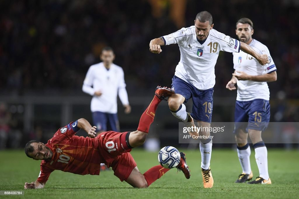 Macedonia's forward Goran Pandev (L) falls as he fights for the ball with Italy's defender Leonardo Bonucci during the FIFA World Cup 2018 qualification football match between Italy and Macedonia on October 6, 2017 at the Grande Torino Stadium in Turin. /