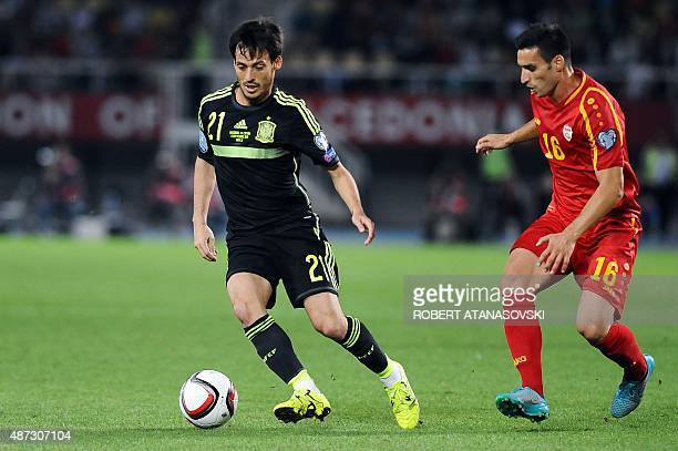 FYR Macedonia's Nikola Gligorov vies with Spain's David Silva during the Euro 2016 Group D qualifying football match between FYR Macedonia and Spain...