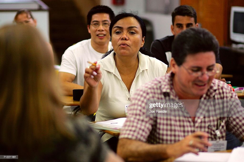 Macela Medina, originally from Colombia, answers a question as she sits in her English class at the English Center June 16, 2006 in Miami, Florida. Gustavo Sabillon, originally from Honduras, sits in front of her. The school holds adult education classes that include English language classes for people who have immigrated to the United States. U.S. President George W. Bush recently said, ?Part of the greatness of America is that we've been able to help assimilate people into our society... And part of that assimilation process is English. I belie ve this: If you learn English, and you're a hard worker, and you have a dream, you have the capacity from going from picking crops to owning the store, or from sweeping office floors to being an office manager.?