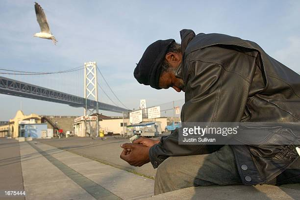 Maceo Grigsby a homeless man sits by the waterfront with the San Francisco Bay Bridge in the background December 5 2002 in San Francisco California...