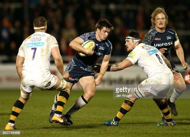 MacGinty of Sale breaks past Guy Thompson and Thomas Young of Wasps during the Aviva Premiership match between Sale Sharks and Wasps at AJ Bell...