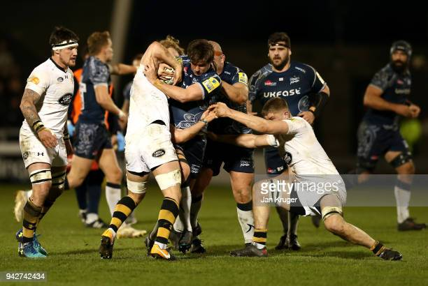 MacGinty of Sale is tackled by Jack Willis and Thomas Young of Wasps during the Aviva Premiership match between Sale Sharks and Wasps at AJ Bell...