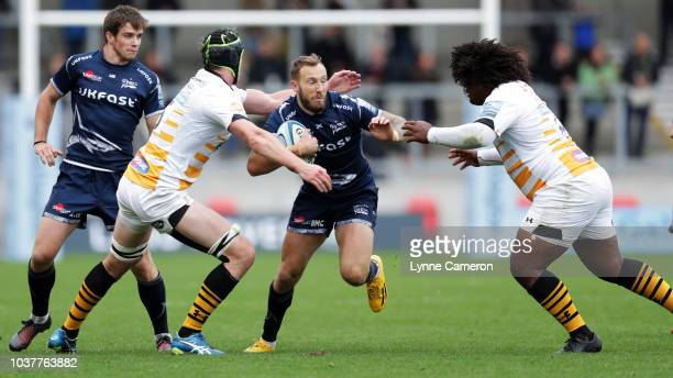 MacGinty of Sale Sharks is tackled by Ashley Johnson and James Gaskell of Wasps during the Gallagher Premiership Rugby match between Sale Sharks and...