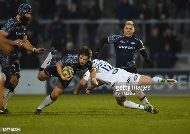 MacGinty of Sale Sharks is tackled by Rhys Priestland of Bath Rugby during the Aviva Premiership match between Sale Sharks and Bath Rugby at AJ Bell...