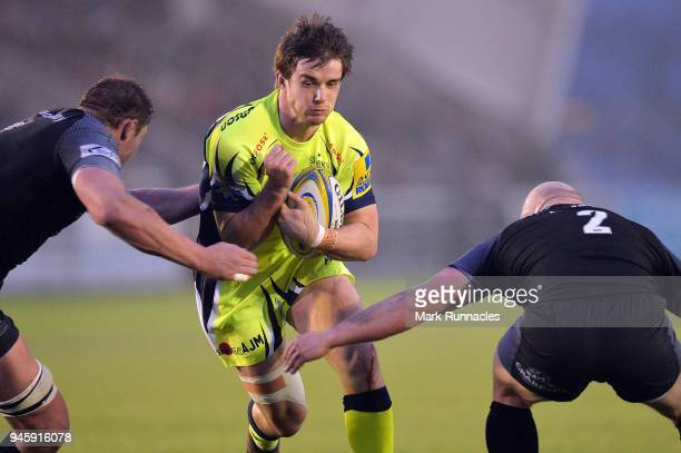 MacGinty of Sale Sharks is tackled by Scott Lawson and Will Welch of Newcastle Falcons during the Aviva Premiership match between Newcastle Falcons...