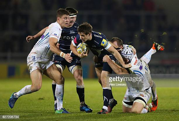 MacGinty of Sale Sharks is tackled by Thomas Waldrom of Exeter Chiefs during the Aviva Premiership match between Sale Sharks and Exeter Chiefs at AJ...