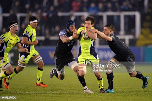 MacGinty of Sale Sharks is tackled by Will Welch and Scott Wilson of Newcastle Falcons during the Aviva Premiership match between Newcastle Falcons...