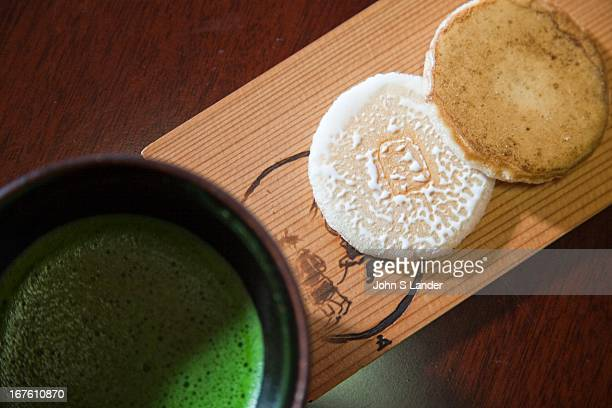 Macha a special type of Japanese green tea served at tea ceremony served up with tea biscuits on a wooden tray