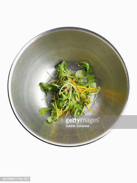 Mache salad in aluminum bowl on white background