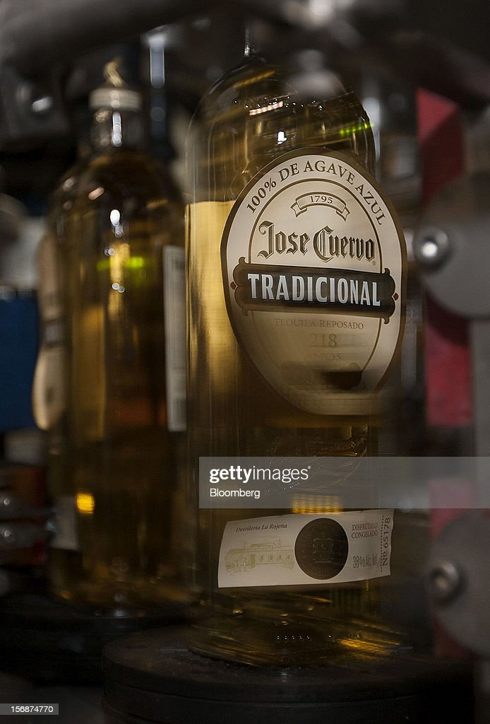 A machine adds the label to a bottle of Jose Cuervo Tradicional on the production line at the Tequila Cuervo La Rojena S.A. de C.V. bottling factory in Guadalajara, Mexico, on Thursday, Nov. 22 2012. There are more than 200 types of agave in Mexico, but use of the blue agave plant was made compulsory in the last century to the issuance of the Official Mexican Standard for Tequila production. Photographer: Susana Gonzalez/Bloomberg via Getty Images