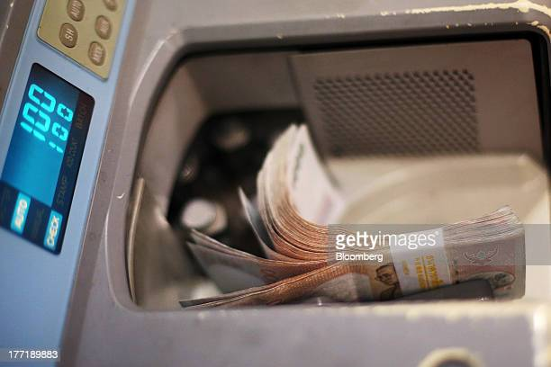A machine counts Thai onethousand baht banknotes at a Super Rich 1965 Co currency exchange store in Bangkok Thailand on Thursday Aug 22 2013...