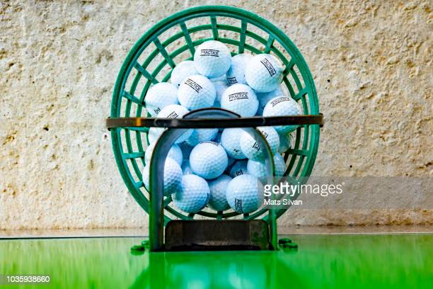 machine filling the basket with golf balls on driving range - ゴルフ練習場 ストックフォトと画像