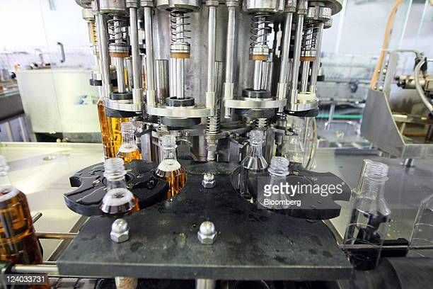 A machine fills bottles with apple vinegar at the Nectar doo fruit beverage making factory in Backa Palanka Serbia on Wednesday Sept 7 2011 Serbia's...
