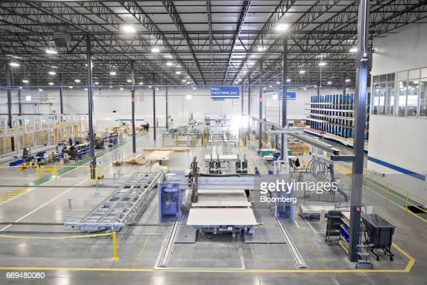 A machine foreground cuts holes into drywall in the wall sheathing area of the Blueprint Robotics facility in Baltimore Maryland US on Tuesday April...