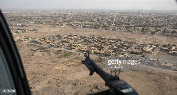 M60 machine gun hangs off the side of a US Army blackhawk helicopter as it flies October 19 2003 over Tikrit Iraq The US Army continues to fight an...