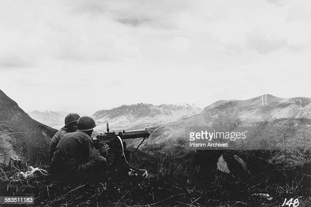 Machine gunners covering caves on opposite hills in Luzon, Philippines, 1940s.