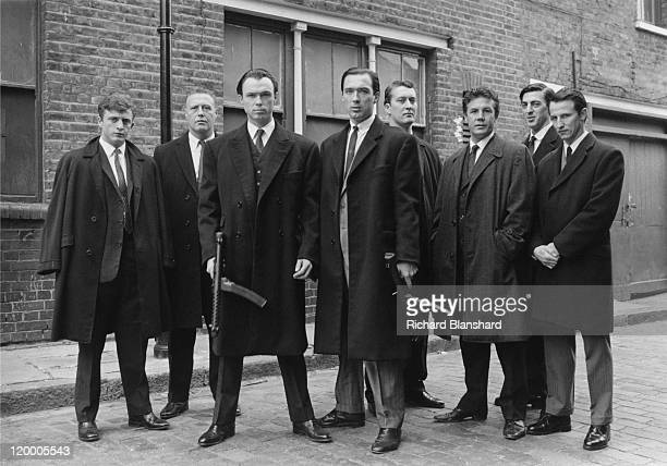 Machine guntoting British gangsters Reggie Kray played by Martin Kemp and Ronnie Kray played by Gary Kemp with members of their gang in 'The Krays'...