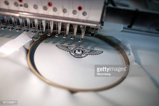 A machine is used to stitch a Bentley logo onto the leather headrest of an automobile at the Bentley Motors Ltd workshop in Crewe UK on Thursday Nov...