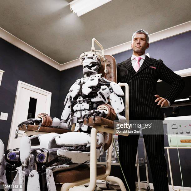 machine learning: businessman with robot undergoing forced mind therapy. - strap stock pictures, royalty-free photos & images