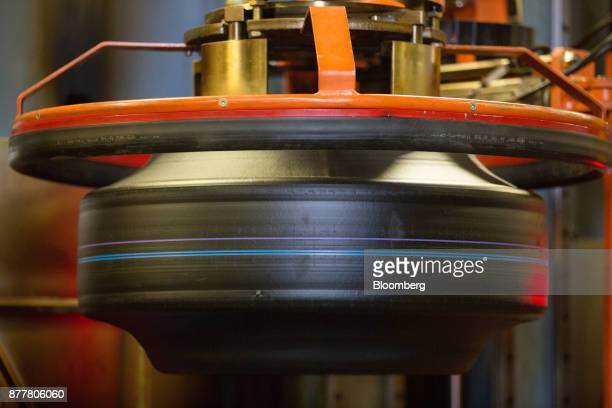 A machine moves a 'green' automobile tire before vulcanization at the Continental AG tire plant in Kaluga Russia on Wednesday Nov 22 2017 The strong...