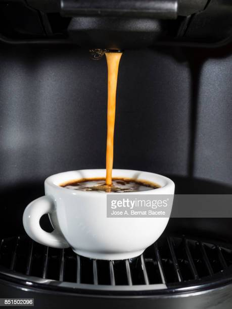 Machine of coffee of capsules with a cup of warm and creamy coffee