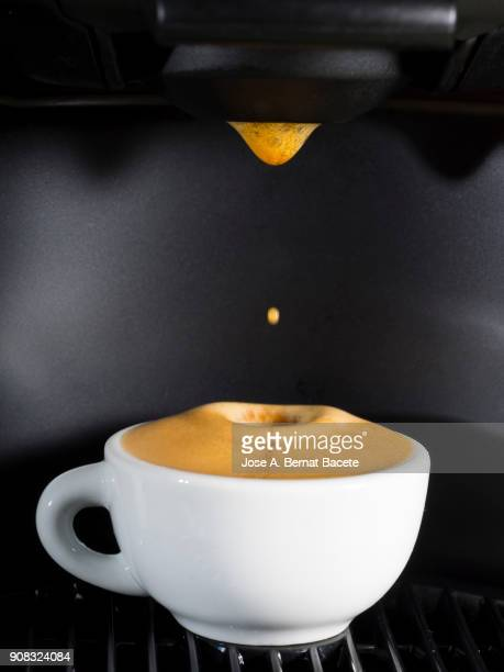 Machine of coffee of capsules with a cup of warm and creamy coffee.