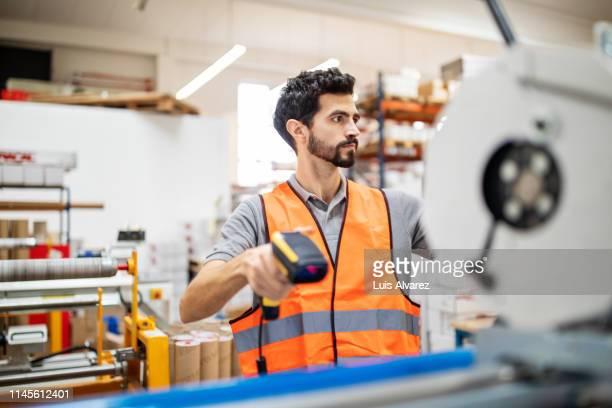 machine operator scanning product - nordafrikanischer abstammung stock-fotos und bilder