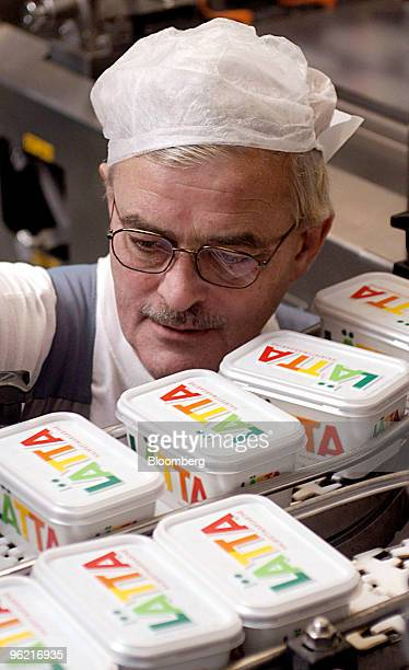 A machine operator watches as boxes of Latta margarine move along a conveyor belt at the Unilever factory in Rotterdam The Netherlands September 16...