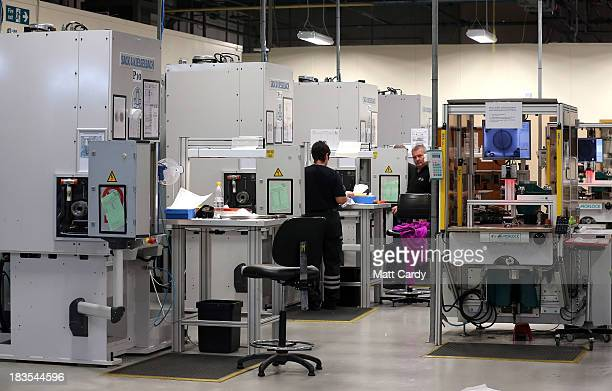 Machine operators work inside The Royal Mint ahead of a new commerative coin being launched on October 7 2013 in Llantrisant Wales This is the first...