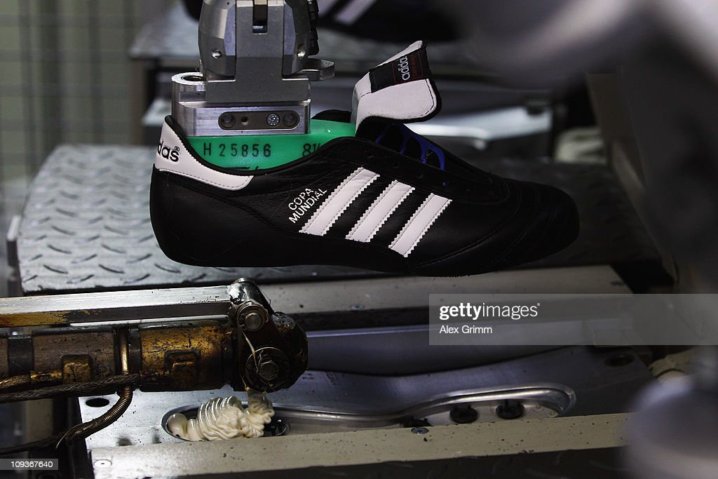 A machine prepares the plastic sole for a handmade Copa Mundial football boot at the factory of German sporting-goods maker Adidas AG on February 23, 2011 in Scheinfeld, Germany. The world's second biggest sports equipment and clothing maker, adidas, will present its 2010 result during a press conference on March 2, 2011.