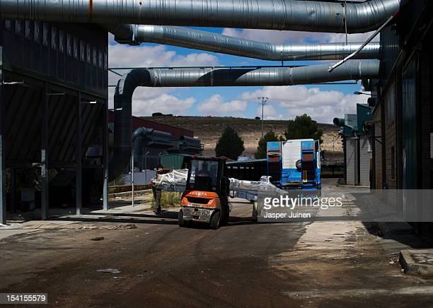 A machine used to make doors is being loaded onto a truck outside a deserted and abandoned hall of one of the former main and now closed door...
