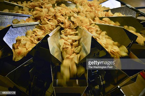 A machine weighs a bag's worth of chips to the gram before moving the chips to be bagged at Route 11 Potato Chips on Thursday March 6 in Mount...