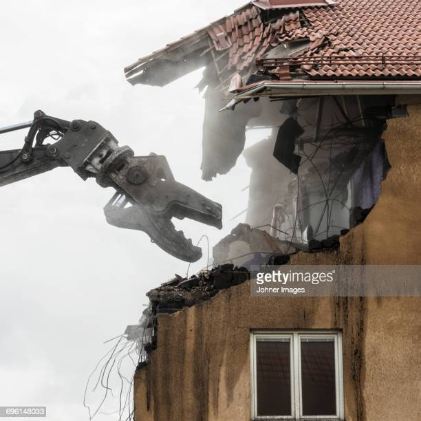 Machinery deconstructing old building