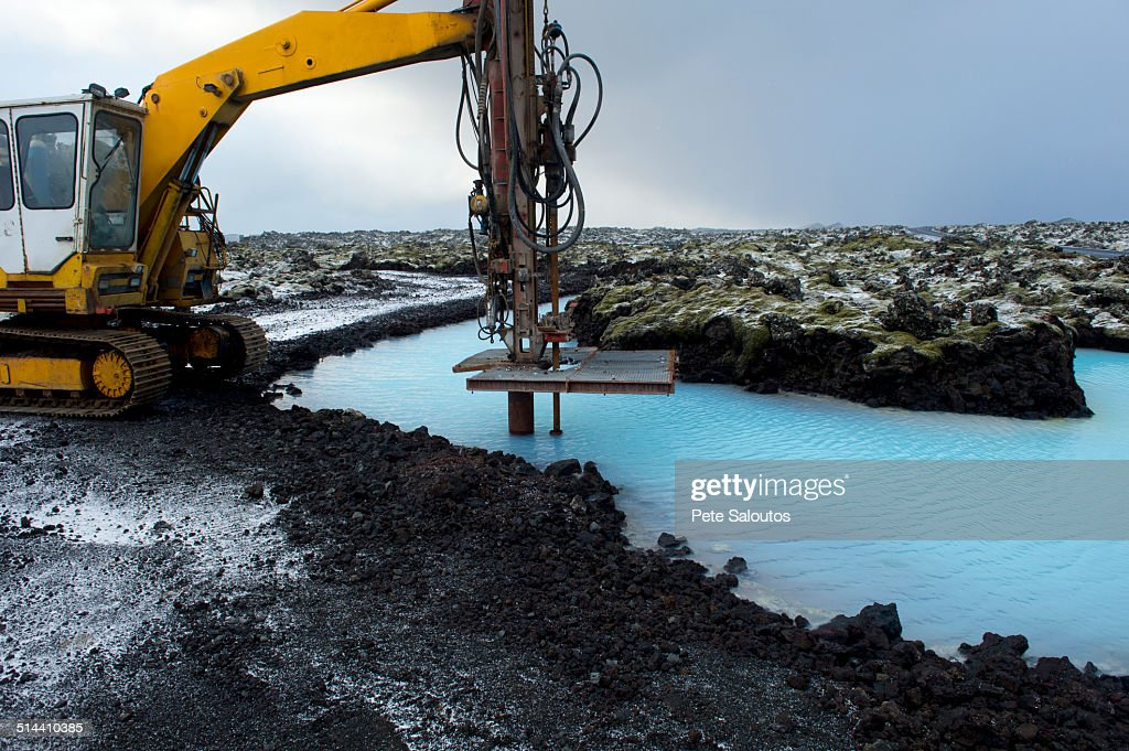 Machinery drilling into lake in arctic landscape : Stock Photo