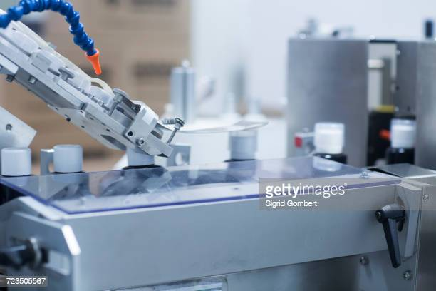 machinery in pharmaceutical plant, placing plastic measuring caps on bottle lids - sigrid gombert stock pictures, royalty-free photos & images