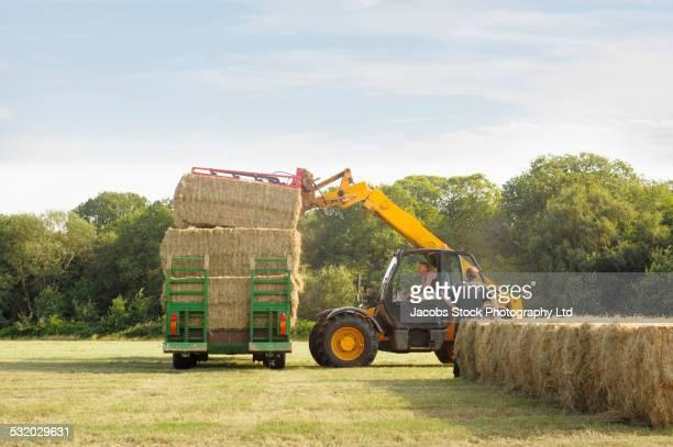 machinery stacking hay bales in farm field - heno fotografías e imágenes de stock