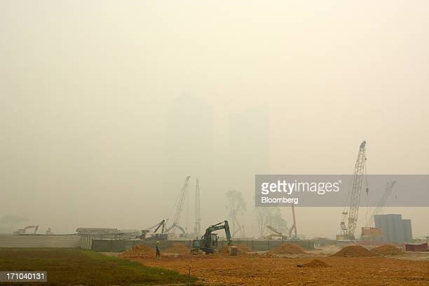 Machinery stand on a construction site at Marina Bay as buildings in the central business district, rear, stand shrouded in smog in Singapore, on...