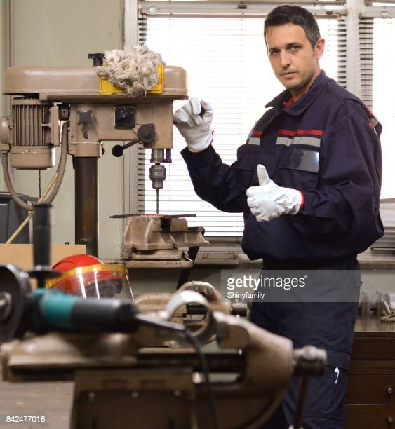 Machinist working on drill in workshop and giving thumbs up