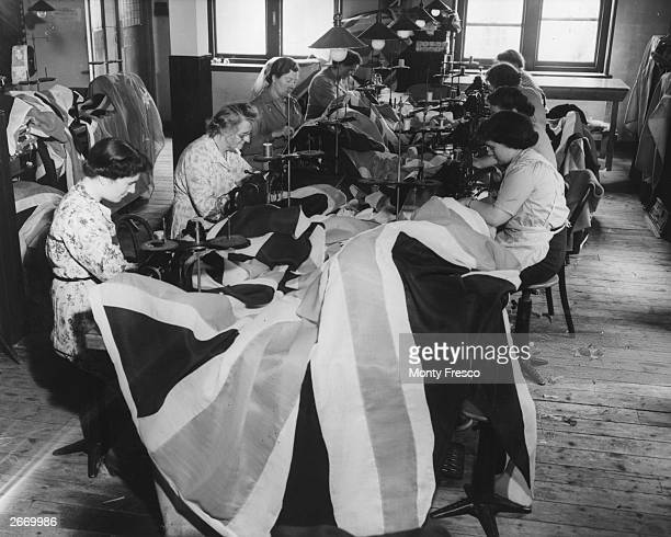 Machinists at work making flags at T C Hayward and Co's premises in the Minories, London, in preparation for Queen Elizabeth II's coronation, 26th...