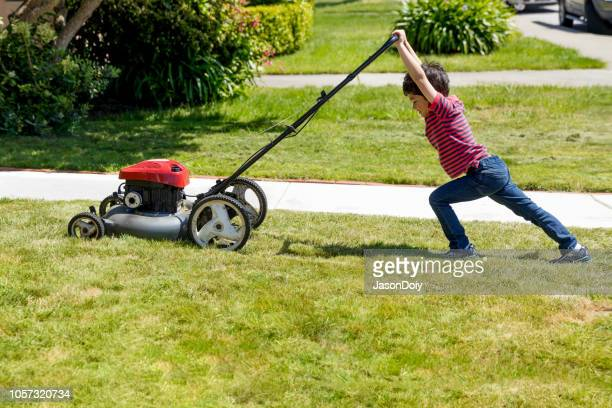 macho kid mows lawn with lawnmower - chores stock pictures, royalty-free photos & images